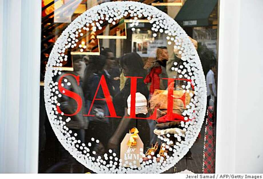 Shoppers are reflected on a shop window announcing sale rate at a shopping mall in Los Angeles, California, on November 30, 2008. According to a poll published on November 28 in USA Today, 33 percent of consumers plan to cut spending this year, about 34 percent will spend the same as last year and only 6.9 percent plan increases, as the Christmas season shopping started. AFP PHOTO/Jewel SAMAD (Photo credit should read JEWEL SAMAD/AFP/Getty Images) Photo: Jewel Samad, AFP/Getty Images
