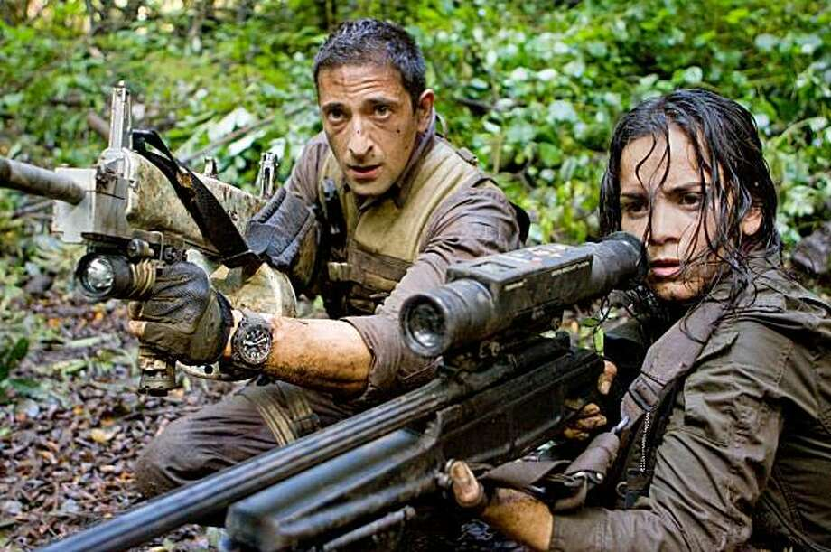 "Royce (Adrien Brody) and Isabelle (Alice Braga) take aim during their desperate battle against the alien Predators in ""Predators."" Photo: Rico Torres, Twentieth Century Fox"