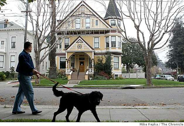 Jason Pollard and his dog Rosie go for their daily walk past a grand looking victorian home in an area called The Gold Coast on, Friday Nov. 28, 2008 in Alameda, Calif. Ran on: 12-07-2008  Ran on: 12-07-2008 Photo: Mike Kepka, The Chronicle
