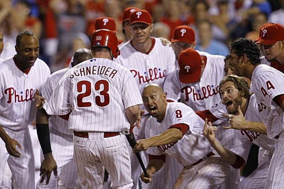 Philadelphia Phillies players celebrate as teammate Brian Schneider (23) crosses home after hitting a game-winning walk off home run off Cincinnati Reds pitcher Jordan Smith in the 12th inning of a baseball game, Thursday, July 8, 2010, in Philadelphia. Philadelphia won 4-3 in 12 innings. Photo: Matt Slocum, AP
