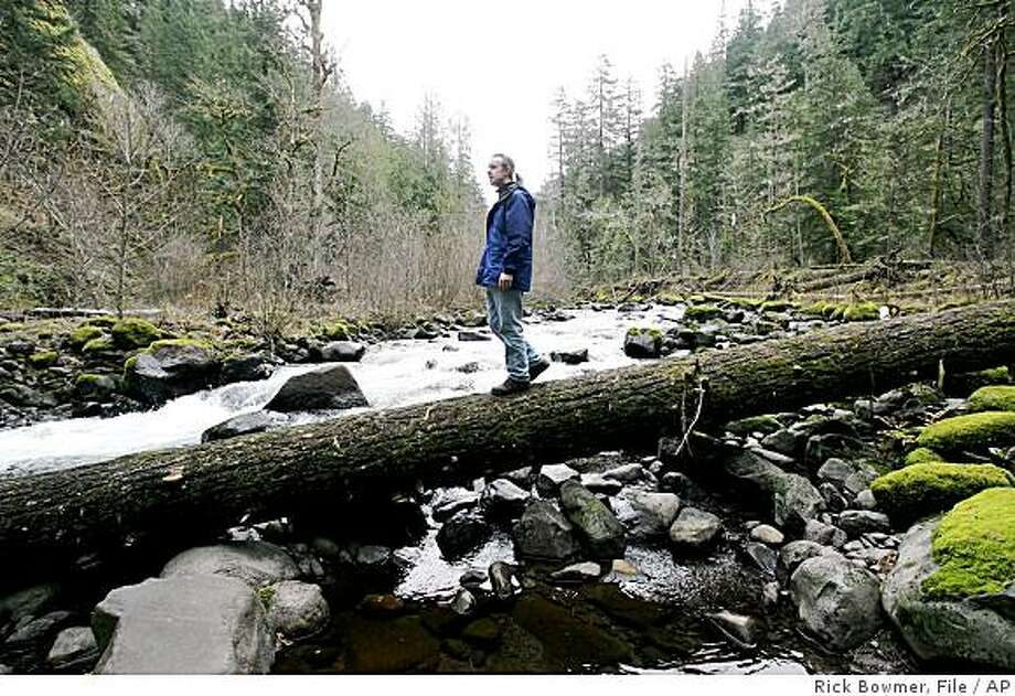 ** FILE **In this file photo taken  Dec. 7, 2005, Erik Fernandez of the conservation group OregonWild crosses Roaring River on the Mount Hood National Forest near Estacada, Ore. After enjoying rising numbers of visitors in the decades following World War II, national forests are seeing a decline in recent years. (AP Photo/Rick Bowmer, File) Photo: Rick Bowmer, File, AP