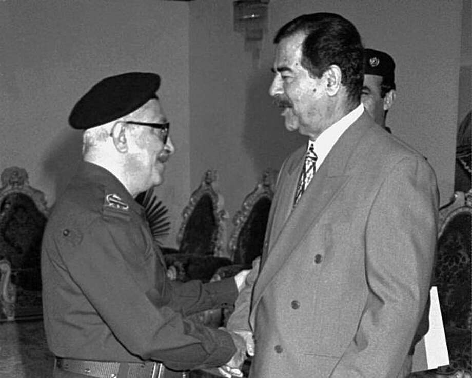 FILE - In this Jan. 29, 1998 file photo, Iraqi Deputy Premier Tariq Aziz, left, greets President Saddam Hussein on Eid al-Fitr, the end of Ramadan in Baghdad, Iraq. Iraq's deputy justice minister says U.S. authorities have handed over 55 members of SaddamHussein's former regime, including the longtime international face of the regime, Tariq Aziz. Photo: Jassim Mohammed, File, AP