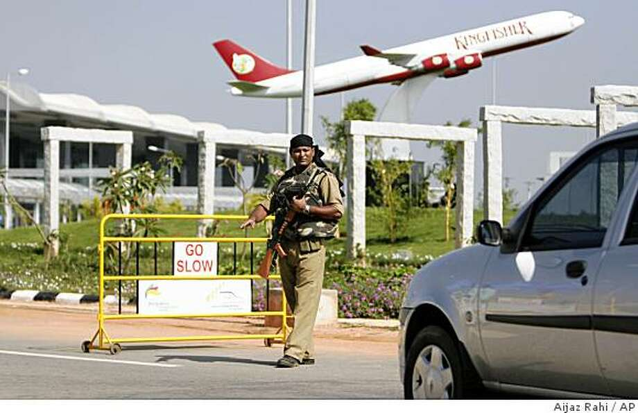 An Indian paramilitary soldier asks a vehicle to stop at a newly installed checkpoint at the Bengaluru International Airport in Bangalore, India, Thursday, Dec. 4, 2008. Indian airports were put on high alert after the government received warnings of possible airborne attacks. In the background is a model of an aircraft. (AP Photo/Aijaz Rahi) Photo: Aijaz Rahi, AP