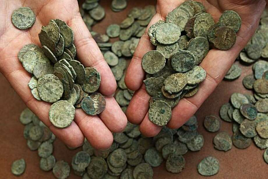 A staff member displays handfuls of coins of Tetricus I (AD271-4 ) on display at the British Museum in London, Thursday, July 8, 2010. About 52,500 Roman coins were found in a large pot by a British treasure hunter Dave Crisp using a metal detector in a field in southwest England, one of the largest treasure hoards ever found in Britain. Crisp found the coins dating from the third century AD, and is valued at 3.3 million pounds ($5 million), includes hundreds of coins bearing the image of Marcus AureliusCarausius, the Roman naval officer who seized power in 286 and proclaimed himself emperor of Britain and northern France, ruling until he was assassinated in 293. Photo: Sang Tan, AP