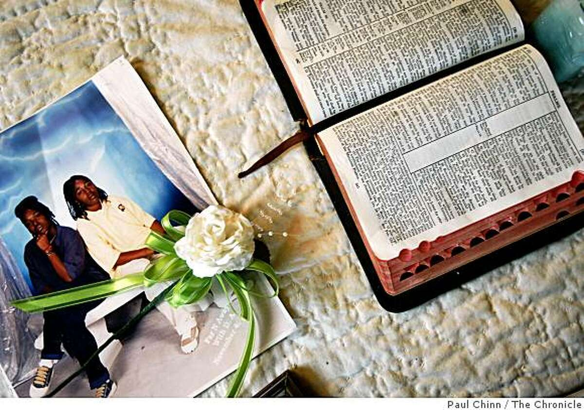 A photo of two of her daughters and an open Bible are displayed on Carol Frazier's coffee table at her home in Vallejo.