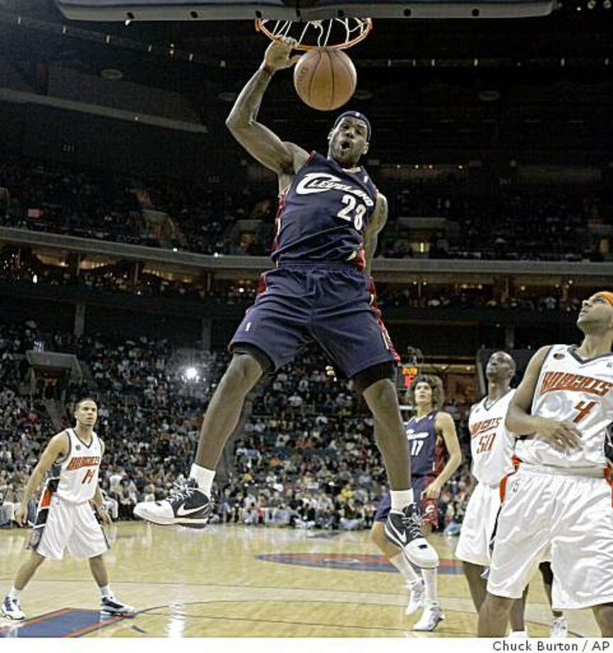 Cleveland Cavaliers forward LeBron James (23) dunks as Charlotte Bobcats forward Jared Dudley (4) looks on during the first half of an NBA basketball game in Charlotte, N.C., Saturday, Dec. 6, 2008. (AP Photo/Chuck Burton) Photo: Chuck Burton, AP