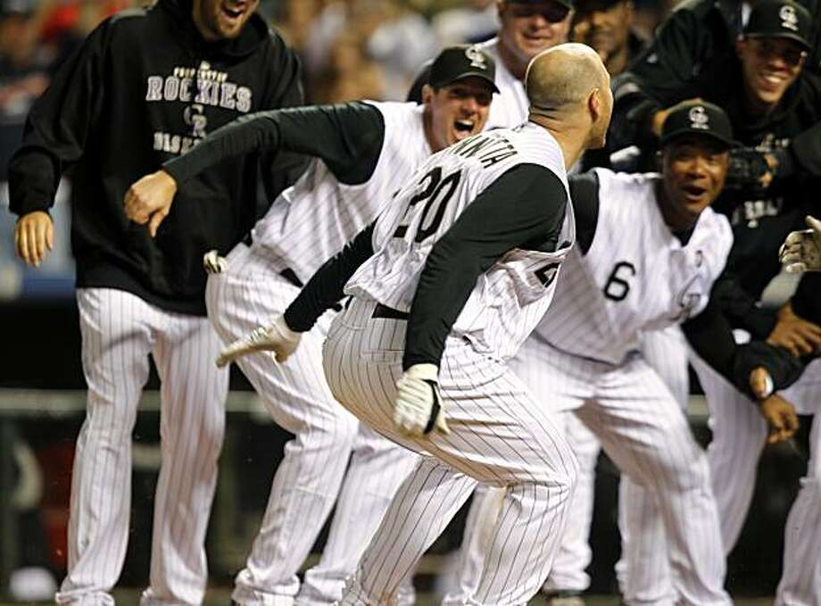 Colorado Rockies' Chris Iannetta, front, celebrates his solo, walk off home run with teammates as they wait at home plate in the ninth inning of the Rockies' 8-7 victory over the St. Louis Cardinals in a baseball game in Denver on Wednesday, July 7, 2010. Photo: David Zalubowski, AP