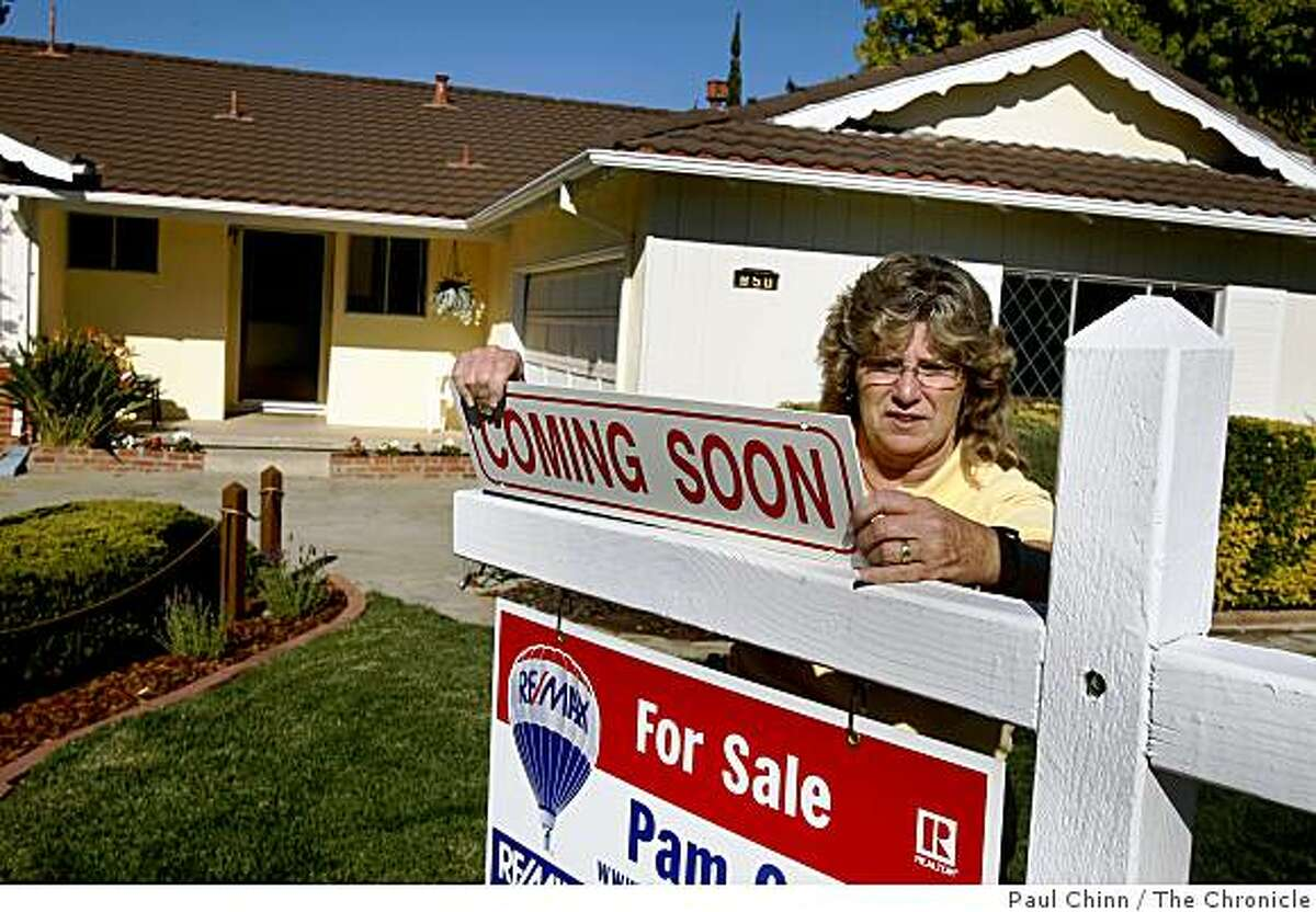 Realtor Pam Cole hangs a sign in front of a house about to hit the market at $495,000 in Livermore, Calif., on Thursday, Nov. 6, 2008. Home prices per square foot in Livermore's 94550 ZIP code, where this three-bedroom, two-bath property is located, are down 17 percent compared to last year which represents the midpoint of price changes in the Bay Area.