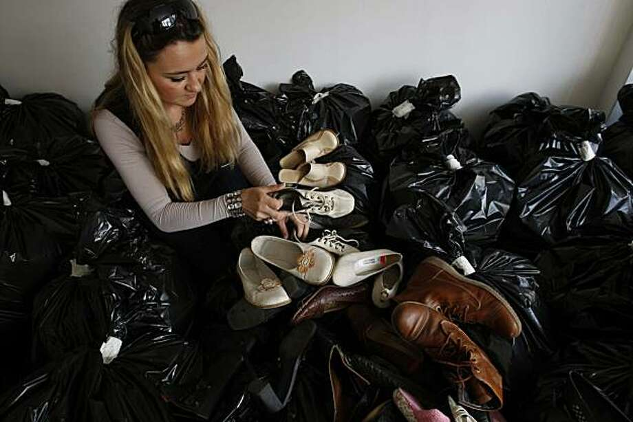 """In this Wednesday, June 30, 2010 photo, a Bosnian activist displays shoes collected to make 'The Pillar of Shame', German activist's Phillip Ruch's monument to Srebrenica, in Sarajevo. A huge jumble of worn shoes, more than 16,000 of them, each pair representing a victim of Europe's worst massacre since World War II, will spell out """"U.N."""" in gigantic letters. The """"Pillar of Shame"""" is to be raised in the hills above the Bosnian town of Srebrenica with a controversial goal: singling out the United Nations and international leaders as the ones most responsible for failing to prevent the mass killings. Photo: Amel Emric, AP"""