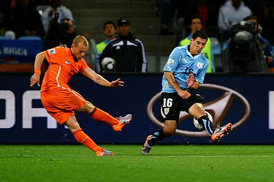 CAPE TOWN, SOUTH AFRICA - JULY 06:  Wesley Sneijder of the Netherlands shoots the ball towards goal, which gets a slight deflection off Maximiliano Pereira of Uruguay and hits the back of the net, scoring his side's second goal during the 2010 FIFA WorldCup South Africa Semi Final match between Uruguay and the Netherlands at Green Point Stadium on July 6, 2010 in Cape Town, South Africa. Photo: Laurence Griffiths, Getty Images