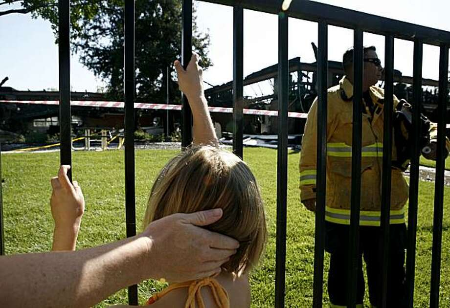 Seven-year-old Gabby Trulson looks at what remains of the building that housed her classroom at Trace Elementary school with her mother, Julie Trulson, nearly twelve hours after a six alarm fire began on Monday, July 5, 2010 in San Jose, Calif. Photo: John Sebastian Russo, The Chronicle