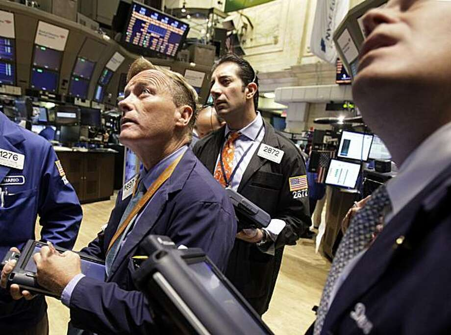 In this photo taken July 8, 2010, traders work on the floor of the New York Stock Exchange. Stock futures fell Friday following a big three-day rally and as investors prepare for upcoming earnings season. Photo: Richard Drew, AP
