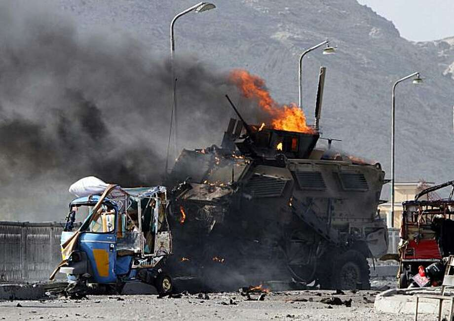 A US military vehicle burns after it was hit by a blast in Jalalabad, east of Kabul, Friday, July 9, 2010. Afghan official said that a suicide car bomb hit the convoy and that one person was killed and nine were wounded. A NATO spokeswoman confirmed an explosion hit a coalition convoy but said she had been told it was a homemade bomb, not a suicide attacker. Photo: Rahmat Gul, Associated Press