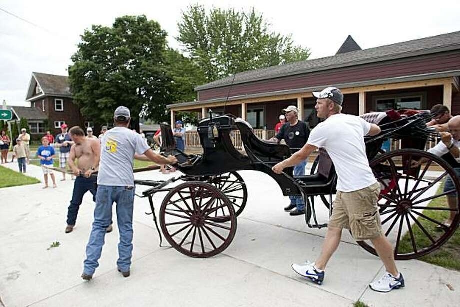 A damaged carriage is moved after the horse that was pulling it got loose, trampling many parade goers at a Fourth of July parade in downtown Bellevue, Iowa, on Sunday, July 4, 2010. The Dubuque Telegraph Herald reported at least 13 people were injured, including several children. (AP Photo/The Telegraph Herald, Mike Burley) MANDATORY CREDIT, TV OUT, MAGS OUT Photo: Mike Burley, AP