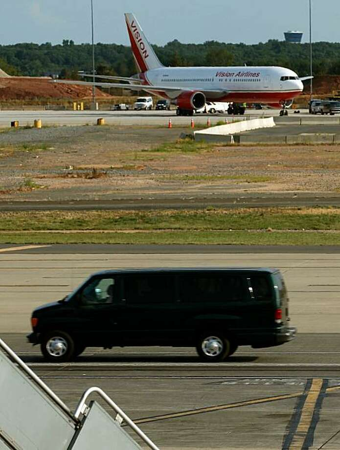 CHANTILLY, VA - JULY 09:  A van with tinted windows carries passengers away from a Vision Airlines jet on the tarmac at Dulles International Airport July 9, 2010 in Chantilly, Virginia. The plane is reportedly carrying a number of Russians convicted of spying for the West, who were traded in Vienna this morning for 10 convicted Russian sleeper agents apprehended in the U.S. Photo: Chip Somodevilla, Getty Images