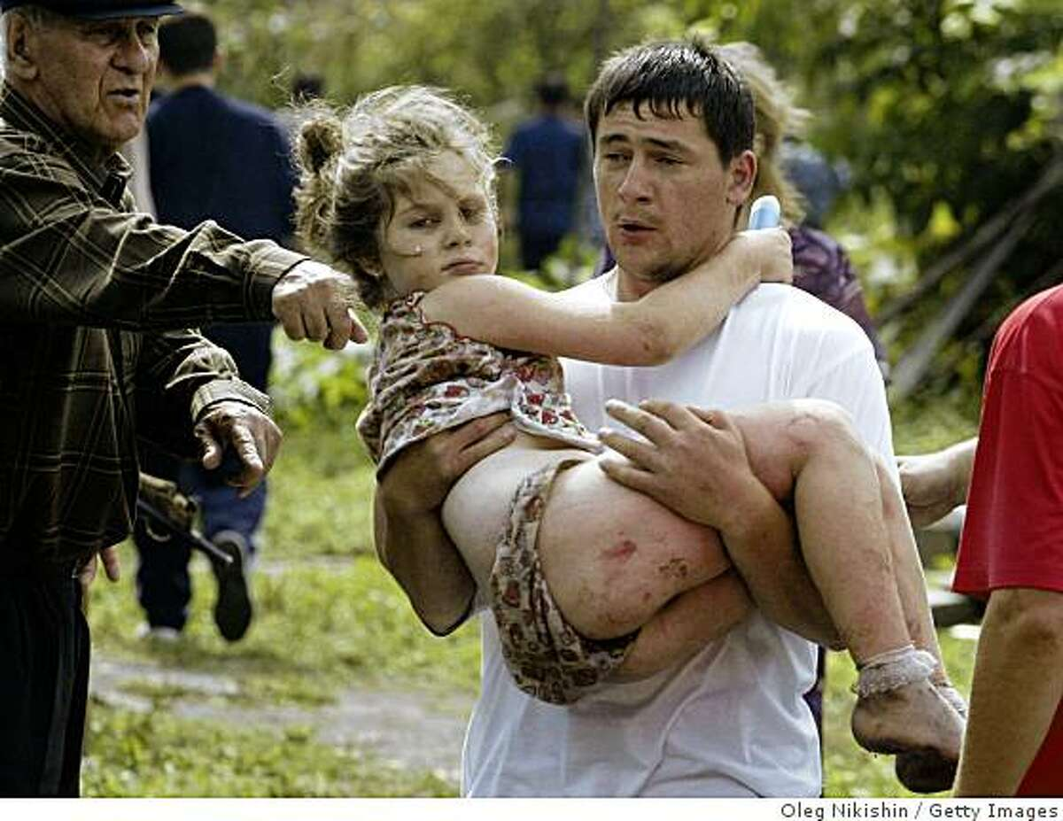 BESLAN, RUSSIA - SEPTEMBER 3: A volunteer carries an injured girl after special forces stormed a school seized by Chechen separatists on September 3, 2004 in the town of Beslan, Russia. Unconfirmed reports state that at least 100 bodies have been discovered inside the school which was taken by Chechyen seperatists on September 1, the beginning of the russian school year. (Photo by Oleg Nikishin/Getty Images)