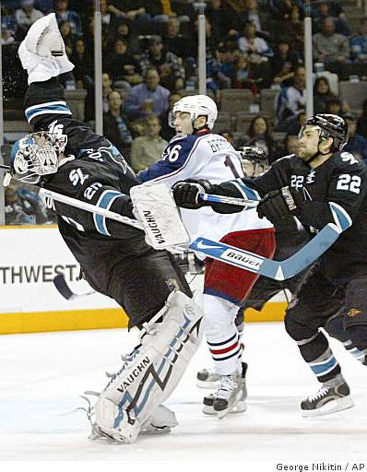 San Jose Sharks goaltender Evgeni Nabokov, left, catches the puck in front of Columbus Blue Jackets' Derick Brassard and Sharks' Dan Boyle in the first period of a game on Thursday, Dec. 4, 2008, in San Jose, Calif. Photo: George Nikitin, AP
