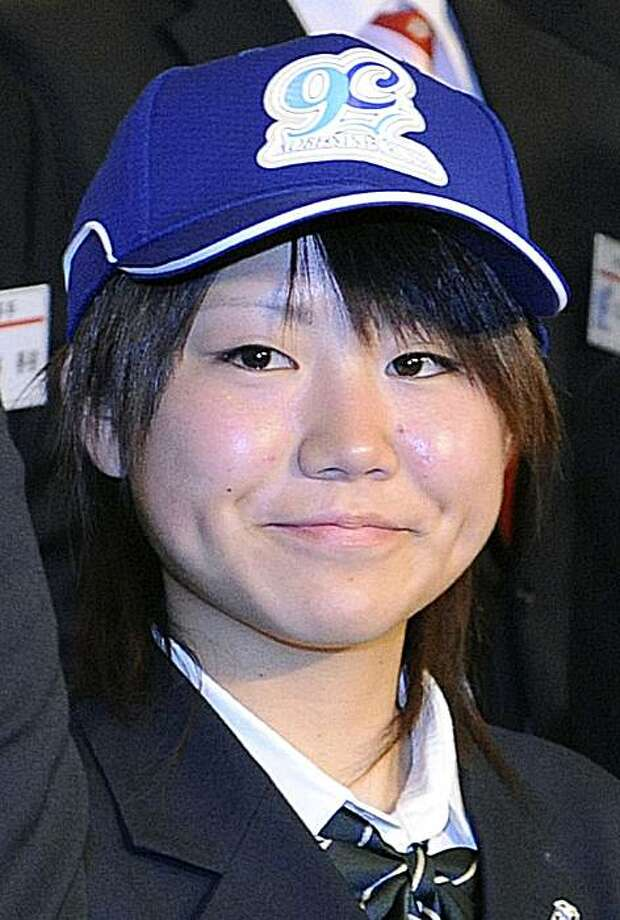 Eri Yoshida, a 16-year-old Japanese girl, poses wearing a Kobe 9 Cruise cap during a press conference in Kobe, western Japan, Tuesday, Dec. 2, 2008. Yoshida, a knuckleball pitcher, signed with the regional baseball team Tuesday, becoming the country's first female professional baseball player. She will play for the Kobe 9 Cruise in a new independent league starting in April 2009. Photo: Kyodo News, AP