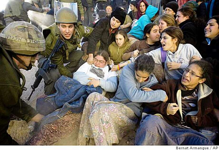 Israeli police officers and soldiers scuffle with girls supporting the Jewish settler movement during the evacuation of a disputed house in the West Bank city of Hebron, Thursday, Dec. 4 2008. Israeli security forces stormed the house in the biblical city of Hebron, dragging out some 250 settlers who barricaded themselves inside and hurled rocks, eggs and chemicals at their evictors. It was the first major West Bank evacuation since a violent 2006 confrontation that injured hundreds.(AP Photo/Bernat Armangue) Photo: Bernat Armangue, AP