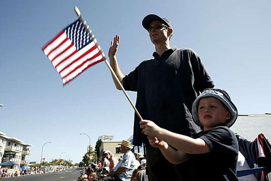 Michael Pence along with his son Owen, four-years-old, wave to participants of the annual Fourth of July Parade on Sunday, July 4, 2010 in Redwood City, Calif. Photo: John Sebastian Russo, The Chronicle