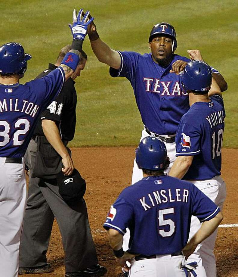 The Texas Rangers' Vladimir Guerrero, top right, is greeted by teammates Josh Hamilton, left, Michael Young, center right, and Ian Kinsler, bottom rigth, at home plate after Gerrero hit a 3-run home run against the Baltimore Orioles in the third inning at Rangers Ballpark in Arlington, Friday, July 9, 2010. (Kelley Chinn/Fort Worth Star-Telegram/MCT) Photo: Kelley Chinn, MCT