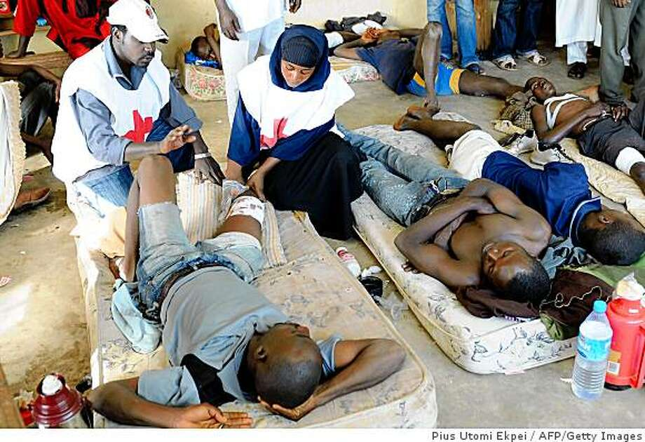 Officials of the Nigerian Red Cross attend to injured victims of the civil unrest in Jos, Plateau State on November 30, 2008. The violence that erupted following the announcement by the Plateau State Independent Electoral Commission of election results into the council polls on the morning of November 28, has left more than three hundred dead in Jos, capital of Plateau State in northcentral Nigeria.Three hundred and forty three dead bodies were buried this morning, said Samaila Mohammed, a member of House of Representatives representing Bassa-Jos North Federal constituency. AFP PHOTO / PIUS UTOMI EKPEI (Photo credit should read PIUS UTOMI EKPEI/AFP/Getty Images) Photo: Pius Utomi Ekpei, AFP/Getty Images