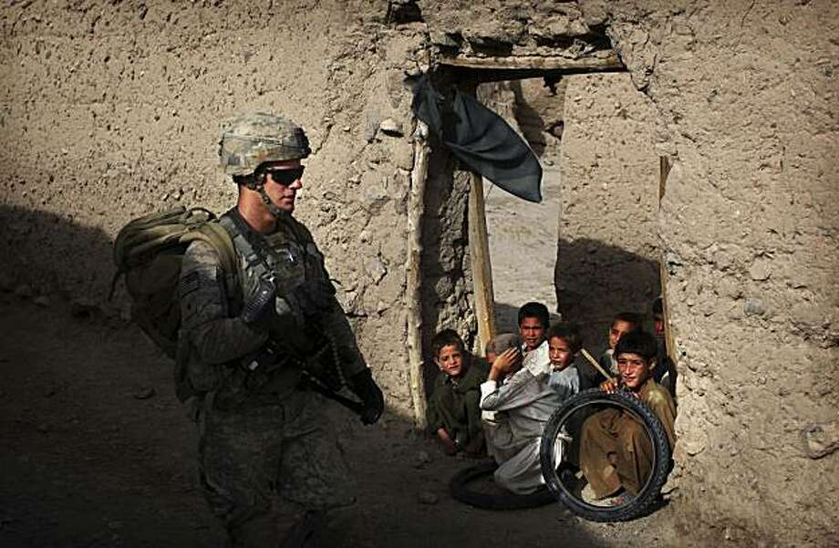 Afghan children watch as a  United States soldier from Bravo Company, 2nd Battalion of the 508 Parachute Infantry Regiment of the 82nd Airborne, walks past during a patrol in the village of Pir-e-Paymal in the volatile Arghandab Valley, outside Kandahar City, Wednesday, July 7, 2010. Photo: Kevin Frayer, AP