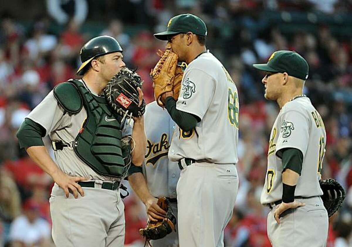 ANAHEIM, CA - MAY 15: Tyson Ross #66, Landon Powell #35 and Daric Barton #10 of the Oakland Athletics meet at the mound in the game against the Los Angeles Angels during the fourth inning at Angels Stadium on May 15, 2010 in Anaheim, California.