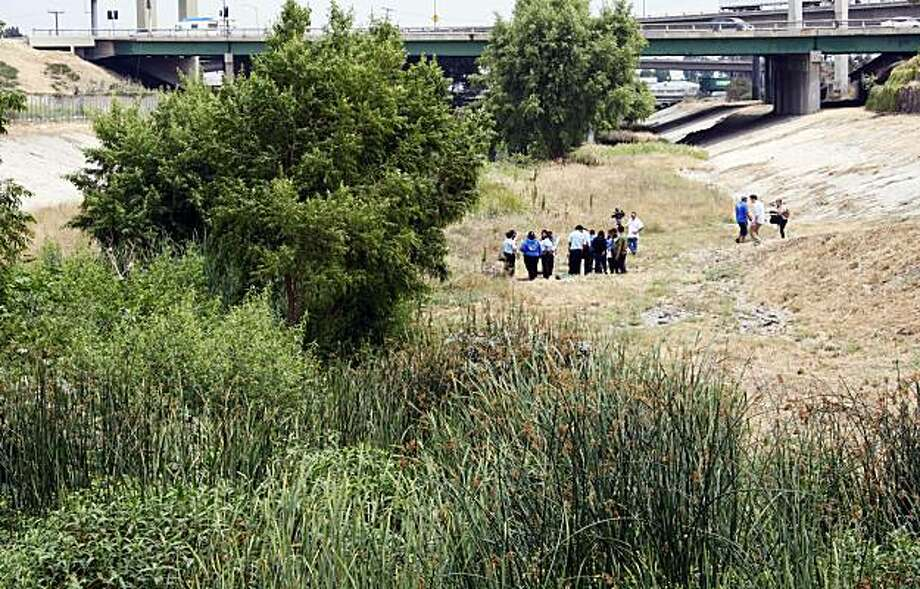 "Students from ""Agua University"" at Compton High School, and others, test water samples as a coalition of public and private stakeholders announce the strategic acquisition of a four-acre ""soft bottom"" parcel of land in Compton Creek, in Compton, Calif., Wednesday, July 7, 2010. The creek is a tributary of the Los Angeles River. Federal officials have affirmed that the Los Angeles River qualifies for Clean Water Act protections by designating it as a full-fledged navigable waterway. Photo: Reed Saxon, AP"