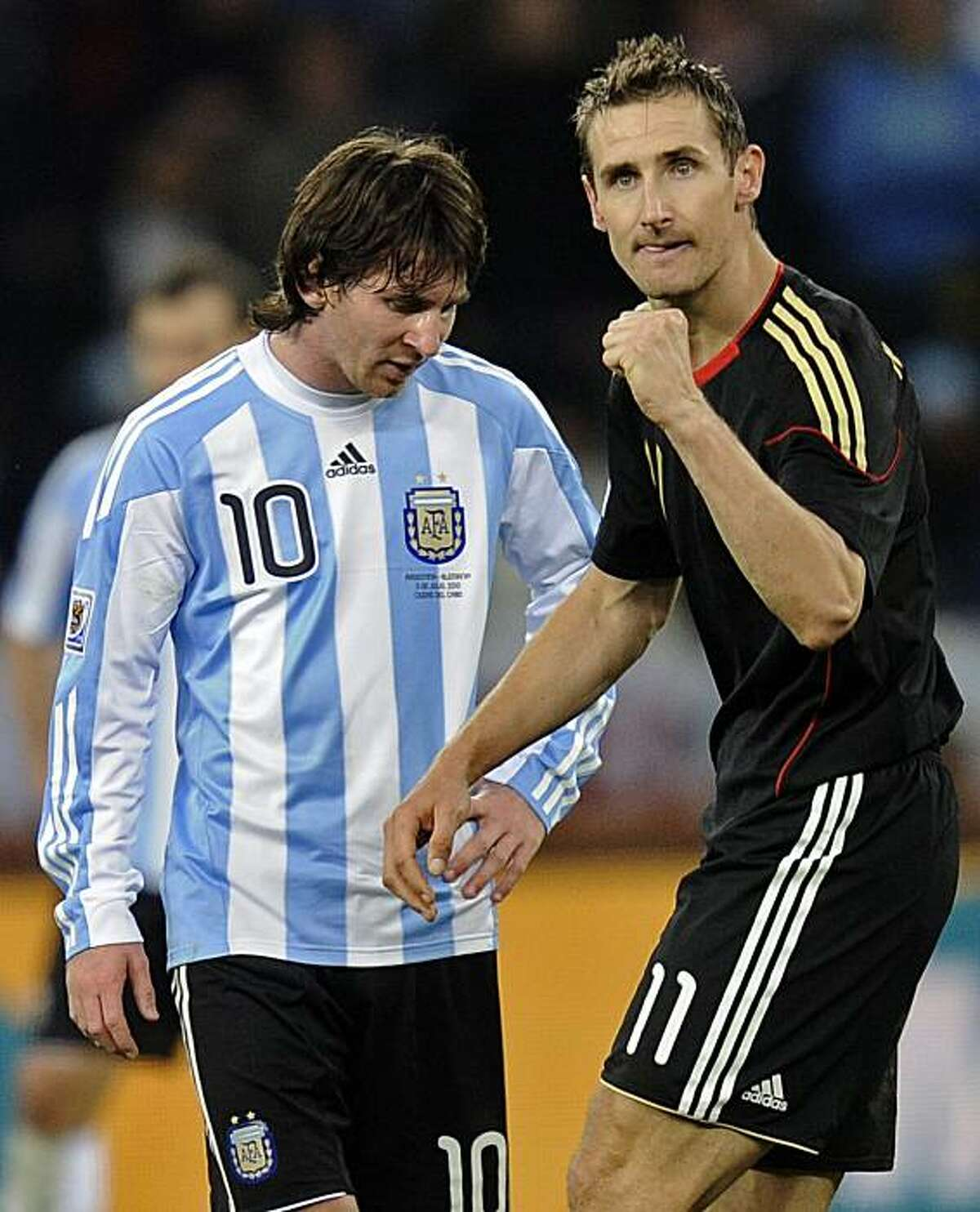 Germany's Miroslav Klose, right, walks past Argentina's Lionel Messi as he celebrates after scoring his team's fourth goal during the World Cup quarterfinal soccer match between Argentina and Germany at the Green Point stadium in Cape Town, South Africa,Saturday, July 3, 2010. Germany won 4-0.