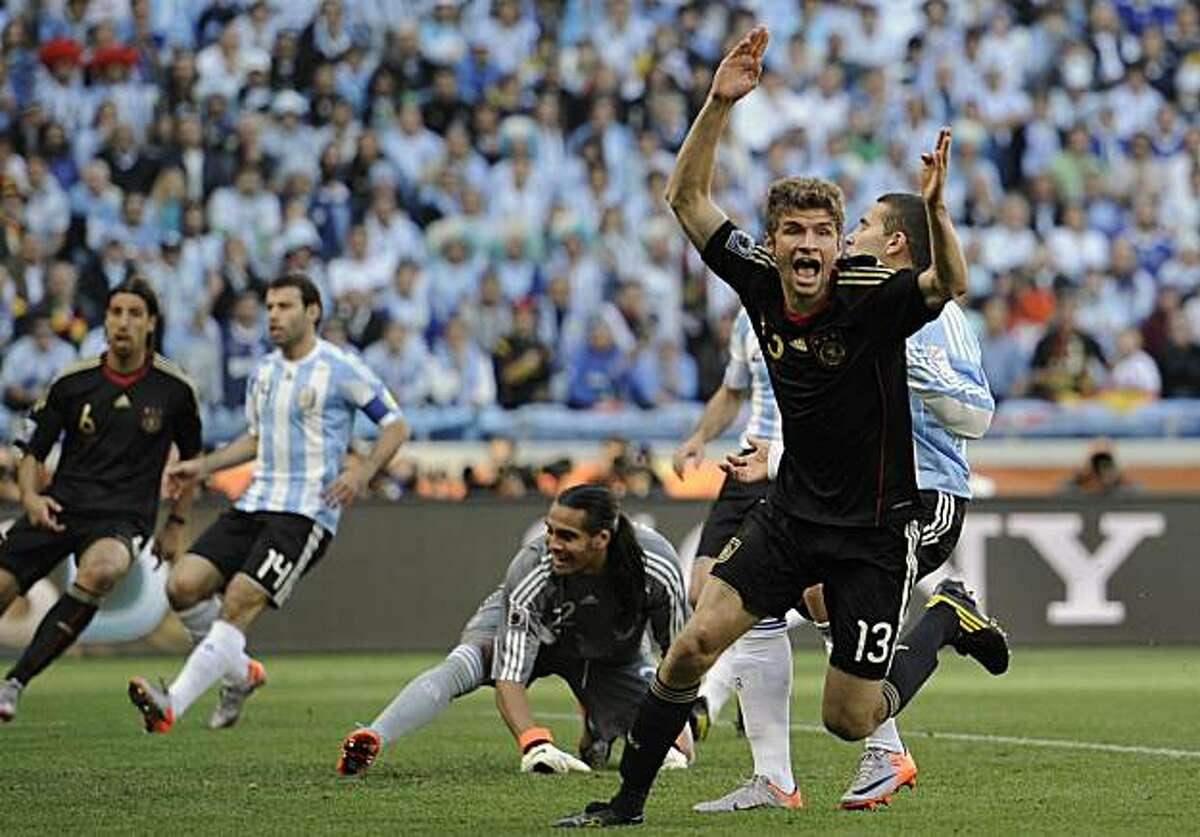 Germany's Thomas Mueller, foreground right, celebrates after scoring a goal during the World Cup quarterfinal soccer match between Argentina and Germany at the Green Point stadium in Cape Town, South Africa, Saturday, July 3, 2010.