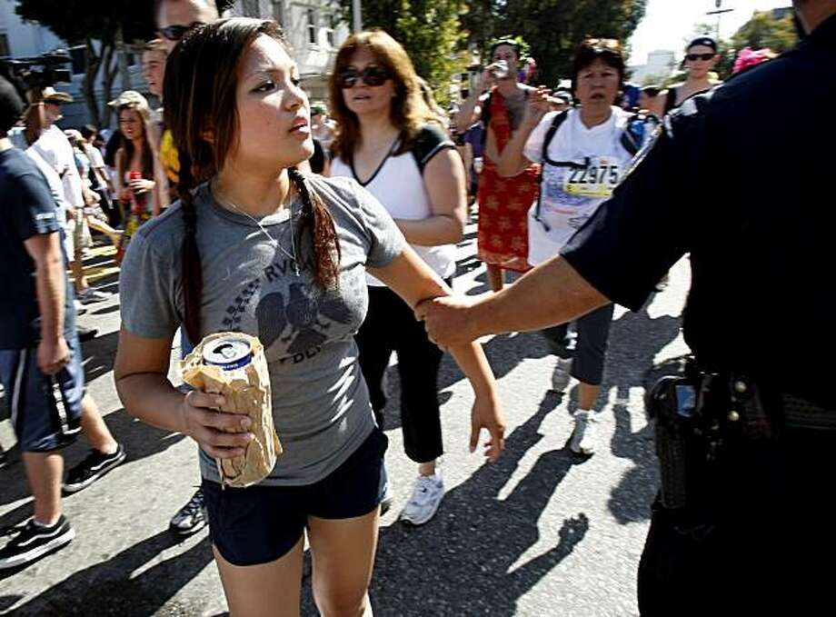 Police stopped people drinking beer at the top of Hayes Street hill and had them throw it out. The 98th running of the Bay to Breakers in San Francisco, CA featured a police crackdown on public drinking. Photo: Brant Ward, The Chronicle