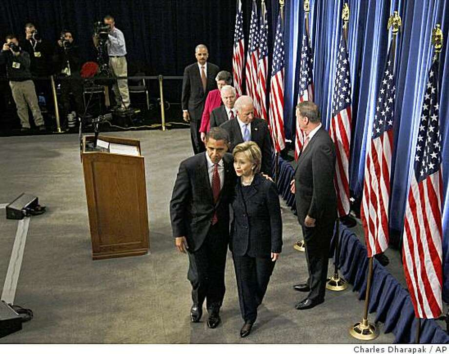 President-elect Barack Obama leaves a news conference with Secretary of State-designate Sen. Hillary Rodham Clinton, D-N.Y., in Chicago, Monday, Dec. 1, 2008. They are followed by, from top left: Attorney General-designate Eric Holder; Homeland Security Secretary-designate, Arizona Gov. Janet Napolitano; Defense Secretary Robert Gates; Vice President-elect Joe Biden; and National Security Adviser-designate Ret. Marine Gen. James Jones. (AP Photo/Charles Dharapak) Photo: Charles Dharapak, AP