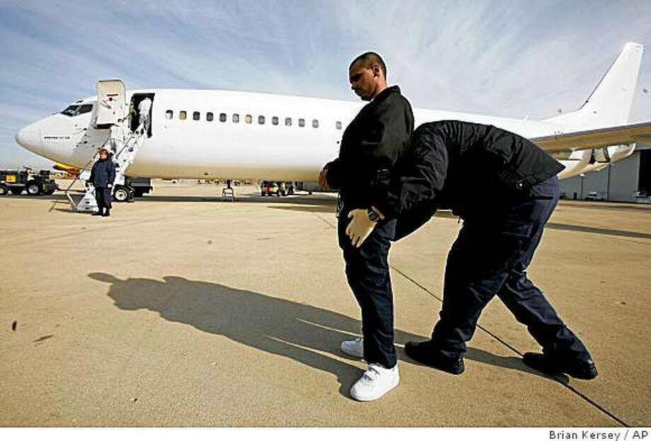 **APN ADVANCE FOR SUNDAY NOV.30**  A U.S. Marshal searches Gerardo Lopez Arellano, 24, before he is escorted to a plane for deportation to Mexico at Chicago's O'Hare International Airport on March 14, 2008. Arellano is one of more than 11,200 immigrants deported this year through Chicago, which handles a six-state region for Immigration and Customs Enforcement. (AP Photo/Brian Kersey) Photo: Brian Kersey, AP