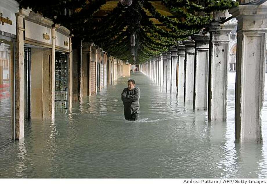 A man walks on Piazza San Marco during floods on December 1, 2008 in Venezia. Authorities in the Italian city of Venice issued a flood alert, warning that the sea was due to rise 1.60 metres above its normal level, the highest for 30 years. Nearly all the streets of the city, including the central tourist district were already under water by mid-morning with the famous Piazza San Marco by 80 centimetres (two feet, seven inches). AFP PHOTO / ANDREA PATTARO (Photo credit should read ANDREA PATTARO/AFP/Getty Images) Photo: Andrea Pattaro, AFP/Getty Images
