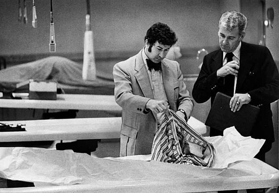 """In this photo from March 29, 1974, San Francisco homicide inspectors David Toschi, left,  and William Armstrong go through a murder victim's clothes at the morgue in the Hall of Justice in San Francisco. The Zodiac killer is blamed for at least five murders in 1968 and 1969 in the San Francisco Bay Area. He was never caught, though many, including Graysmith, believe he was Arthur Leigh Allen, a Vallejo man who  who died in 1992. The $80 million film, """"Zodiac,"""" based on the 1986 true-crime book by Graysmith, was shot in 2005 in the San Francisco Bay area.     (AP Photo/The San Francisco Chronicle, Susan Ehmer) Ran on: 03-01-2007 San Francisco homicide Inspectors David Toschi (left) and William Armstrong go through a victim's clothing in the morgue. Ran on: 03-01-2007 San Francisco homicide Inspectors David Toschi (left) and William Armstrong go through a victim's clothing in the morgue. Ran on: 03-01-2007 San Francisco homicide Inspectors David Toschi (left) and William Armstrong go through a victim's clothing in the morgue. Photo: Susan Ehmer, AP"""