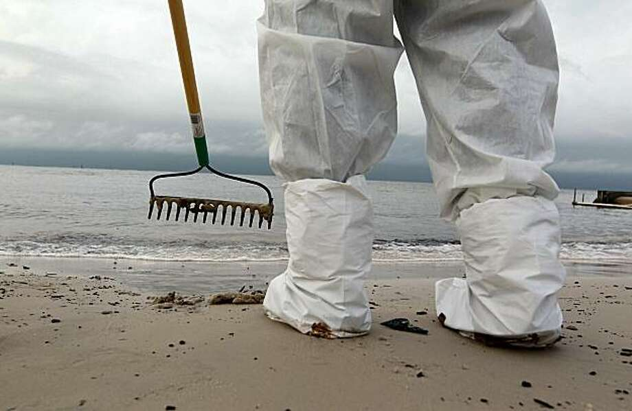 BILOXI, MS - JULY 1:  A worker wears protective gear as he uses a rake to collect oil globs that were washing ashore from the Deepwater Horizon oil spill in the Gulf of Mexico on July 1, 2010 in Biloxi, Mississippi. Hurricane Alex produced high winds andrough seas, hindering the continued efforts to contain the oil spill from the Deepwater Horizon rig. Millions of gallons of oil have spilled into the Gulf since the April 20 explosion on the drilling platform. Photo: Joe Raedle, Getty Images