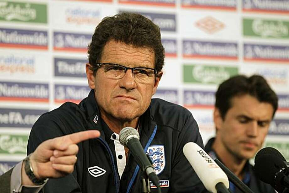England manager Fabio Capello, left, participates in a post-match press conference at Royal Bafokeng Sports Complex outside Rustenburg, South Africa, Monday, June 28, 2010. Christian Lattanzio, team psychologist and a translator for the Italian manager, is seen at right. The English soccer team was eliminated in the World Cup round of 16, after a 4-1 defeat by the Germans. Photo: Rebecca Blackwell, AP