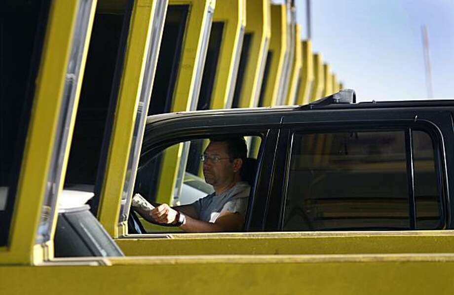 A commuter pays the new $6.00 peak time toll charge at the Bay Bridge toll plaza in Oakland, Calif., on Thursday, July 1, 2010. Thursday was also the first day carpoolers were forced to pay a $2.50 toll. Photo: Paul Chinn, The Chronicle