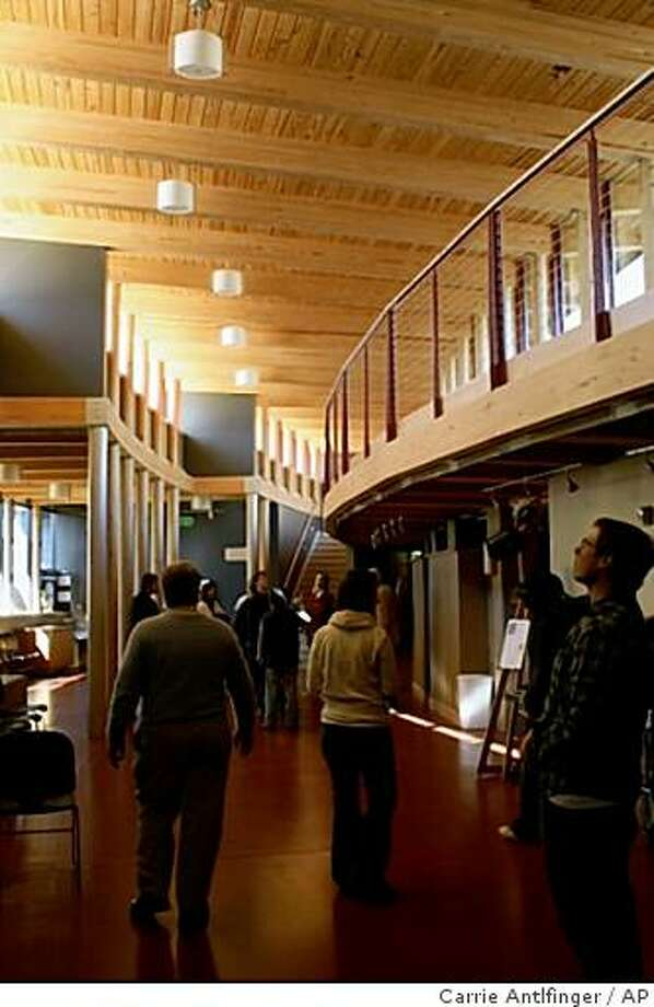 Architectual students walk around the new addition to the First Unitarian Society in Madison, Wis. on Thursday, Oct. 30, 2008. Church officials needed to add on to the original building, designed by Frank Lloyd Wright, to accomodate a growing congregation. (AP Photo/Carrie Antlfinger) Photo: Carrie Antlfinger, AP