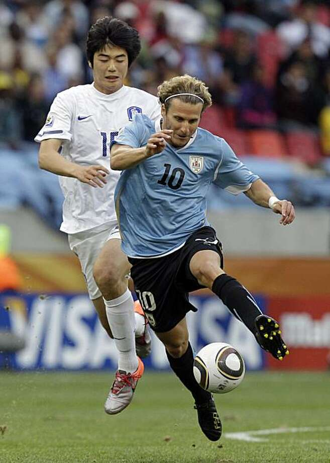 Uruguay's Diego Forlan, front, controls the ball past South Korea's Ki Sung-yong, back, during the World Cup round of 16 soccer match between Uruguay and South Korea at Nelson Mandela Bay Stadium in Port Elizabeth, South Africa, Saturday, June 26, 2010. Photo: Schalk Van Zuydam, AP