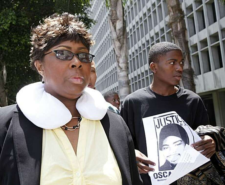 Wanda Johnson, mother of shooting victim, Oscar Grant leaves court during the murder trial of former San Francisco Bay area transit police officer, Johannes Mehserle, accused to shooting Grant on New Year's  Day 2009, Thursday July 1, 2010 in Los Angeles.Demonstrator at right is unidentified. Photo: Nick Ut, AP