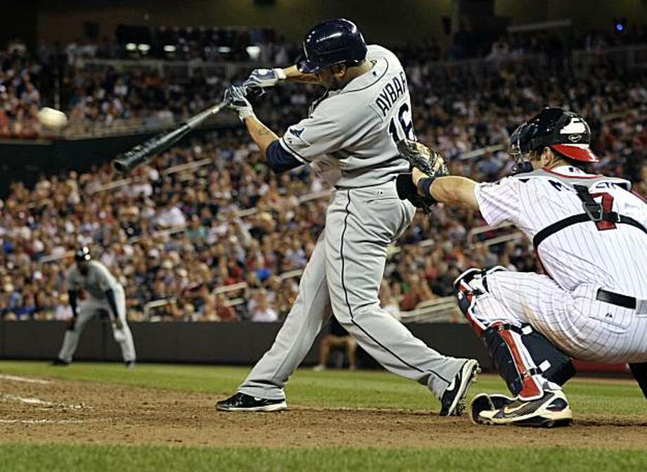 Tampa Bay Rays' Willy Aybar, left, hits an RBI single driving in the Rays' Reid Brignac on a pitch from the Minnesota Twins' Matt Guerrier during the tenth inning of a baseball game Thursday, July 1, 2010 in Minneapolis. Twins catcher Joe Mauer, right, watches. Tampa Bay won 5-4. Photo: Tom Olmscheid, AP