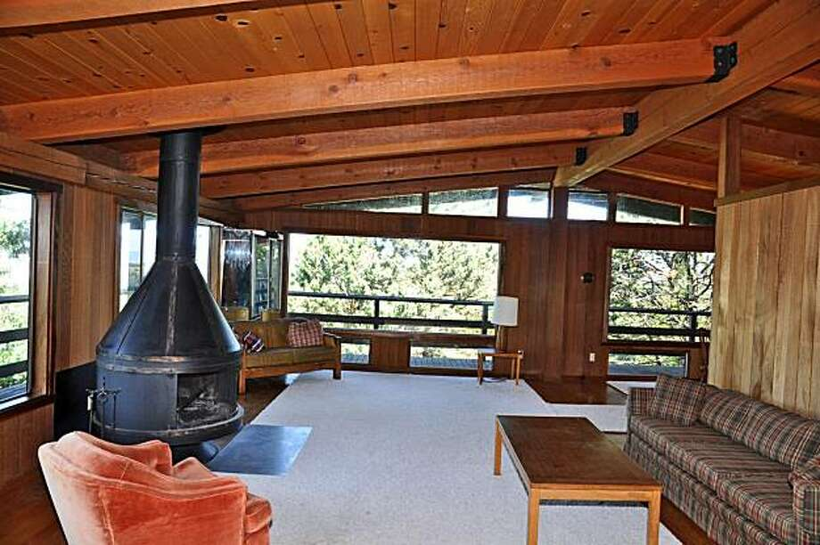 The living room has a vaulted ceiling, a fireplace and wide windows that open to the wraparound deck. It's connected to a dining area. Photo: All Access Photo