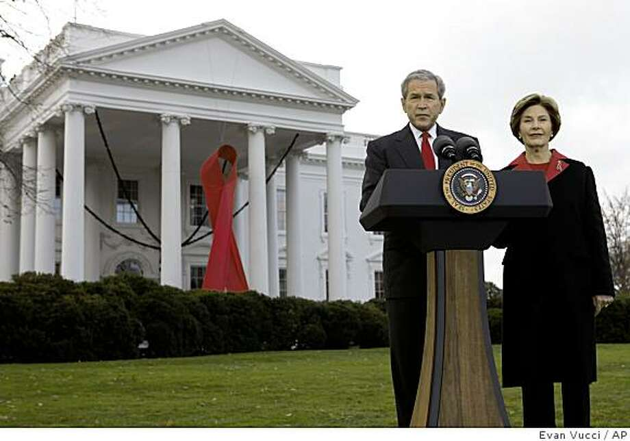 President George W. Bush makes a statement with first lady Laura Bush, right, on World AIDS Day, at the White House in Washington, Monday, Dec. 1, 2008 in Washington.  (AP Photo/Evan Vucci) Photo: Evan Vucci, AP