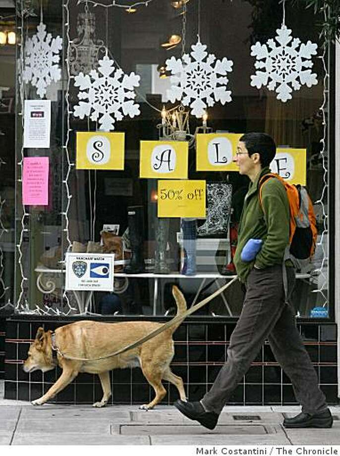 A pedestrian and a dog walk past a 50% off sign on College Ave. in the Rockridge district of Oakland on Black Friday. Photo: Mark Costantini, The Chronicle