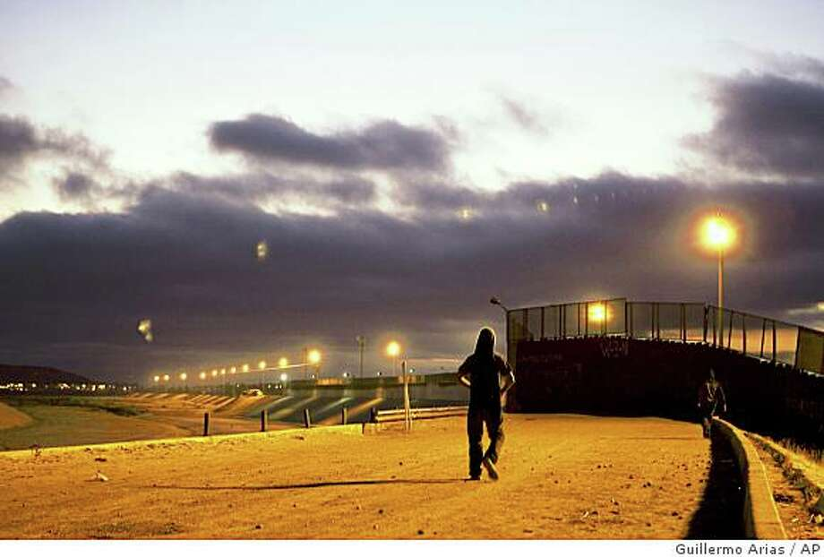 **APN ADVANCE FOR SUNDAY NOV.30**  Part time smuggler Juan Garcia walks in the Tijuana River basin on the Mexican side of the U.S.-Mexico border, in Tijuana, Mexico, Saturday, Aug. 16, 2008.  In this part of the Mexico-US border, United States Border Patrol apprehensions of illegal crosser's have increased 28 percent since 2005,  even as apprehensions have dropped nearly 40 percent border-wide over the same period.(Guillermo Arias) Photo: Guillermo Arias, AP