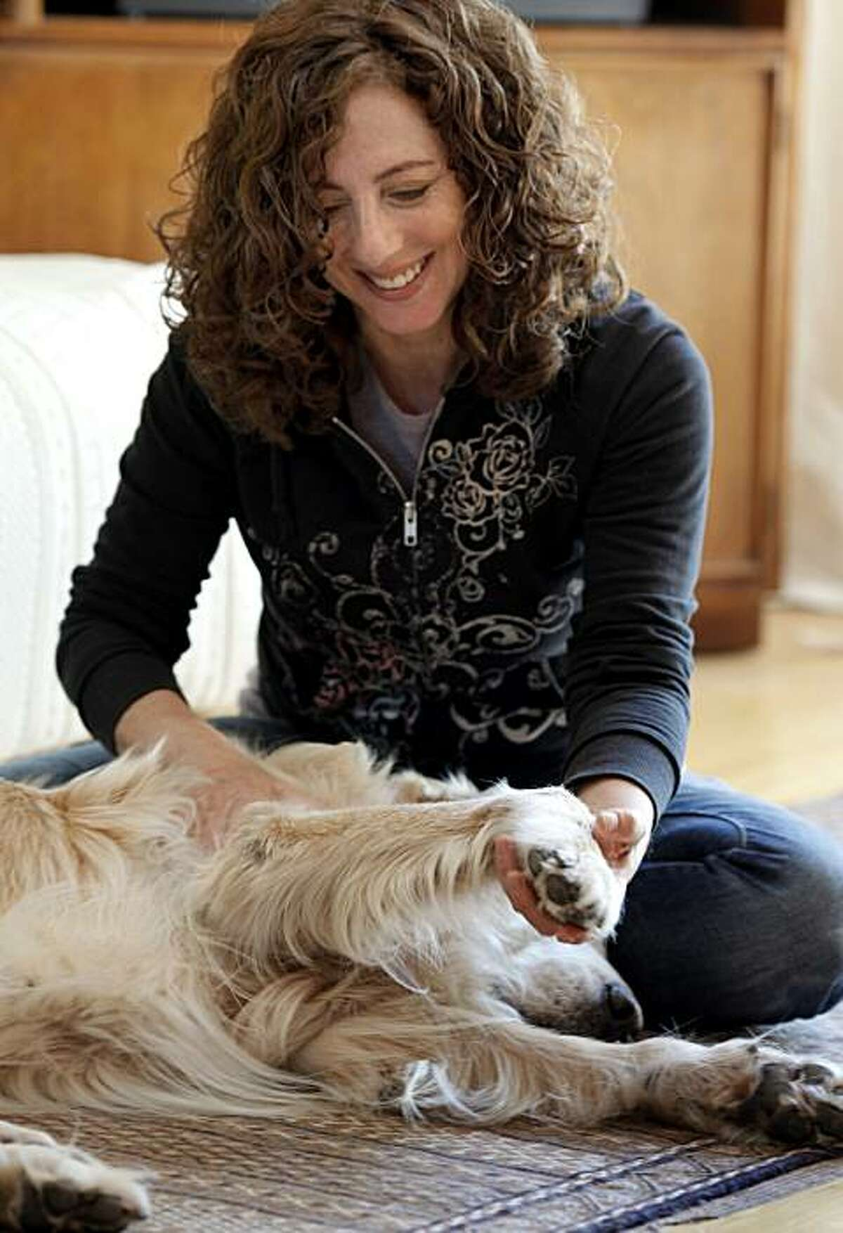 Shelah Barr smiled as she reflected on her unique profession. Shelah Barr massages dogs for a living. She visits with Pico, a 13 year old Golden Retriever, in San Francisco, Calif. Thursday July 1, 2010.