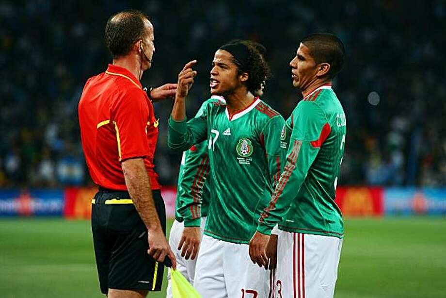 JOHANNESBURG, SOUTH AFRICA - JUNE 27:  Giovani Dos Santos and Carlos Salcido of Mexico appeal to referee assistant Stefano Ayroldi over the Carlos Tevez goal during the 2010 FIFA World Cup South Africa Round of Sixteen match between Argentina and Mexico at Soccer City Stadium on June 27, 2010 in Johannesburg, South Africa. Photo: Laurence Griffiths, Getty Images