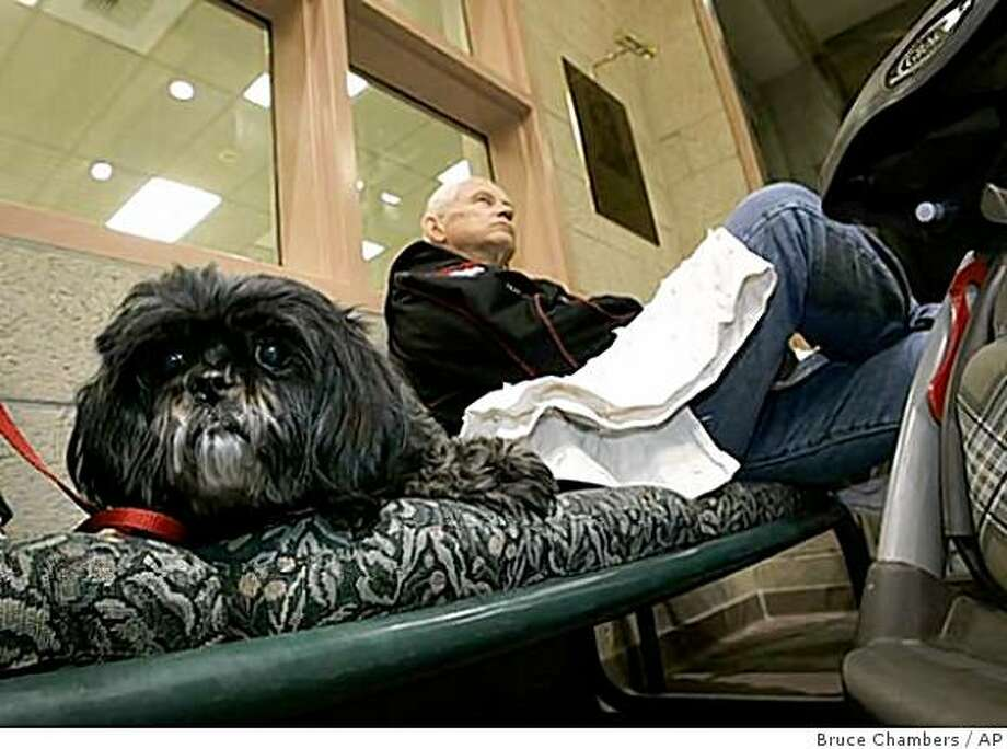 Romy waits  in the lobby of the Thomas Lasorda, Jr. Field House in Yorba Linda, Calif., with his master Greg Friga after they were evacuated from their Yorba Linda home Wednesday morning, Nov. 26, 2008.  The threat of mud flows drove them from their homes inwildfire ravaged neighborhoods of Yorba Linda. (AP Photo/ Orange County Register, Bruce Chambers)**LA TIMES OUT,  NO MAGS,  NO SALES** Photo: Bruce Chambers, AP